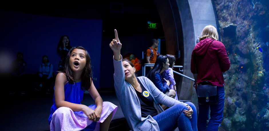 A woman shows an amazed young girl the Philippine Coral Reef exhibit