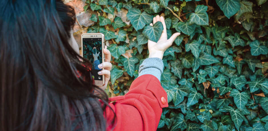A woman uses the iNaturalist app to identify a plant