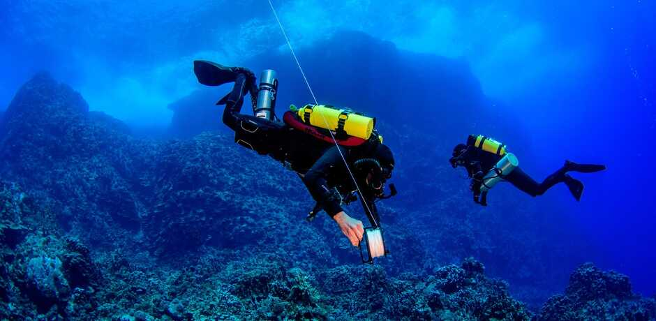 2 scuba divers lay transect lines in Easter Island