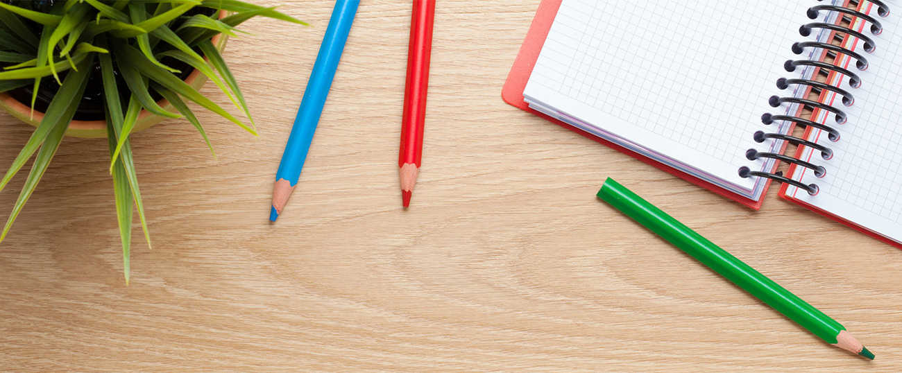 A notebook lies open on a desk, with colored pencils stationed nearby.