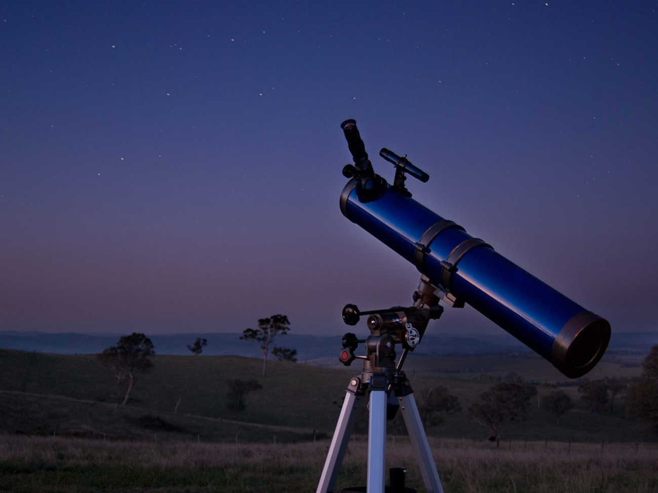 A telescope points to the night sky.
