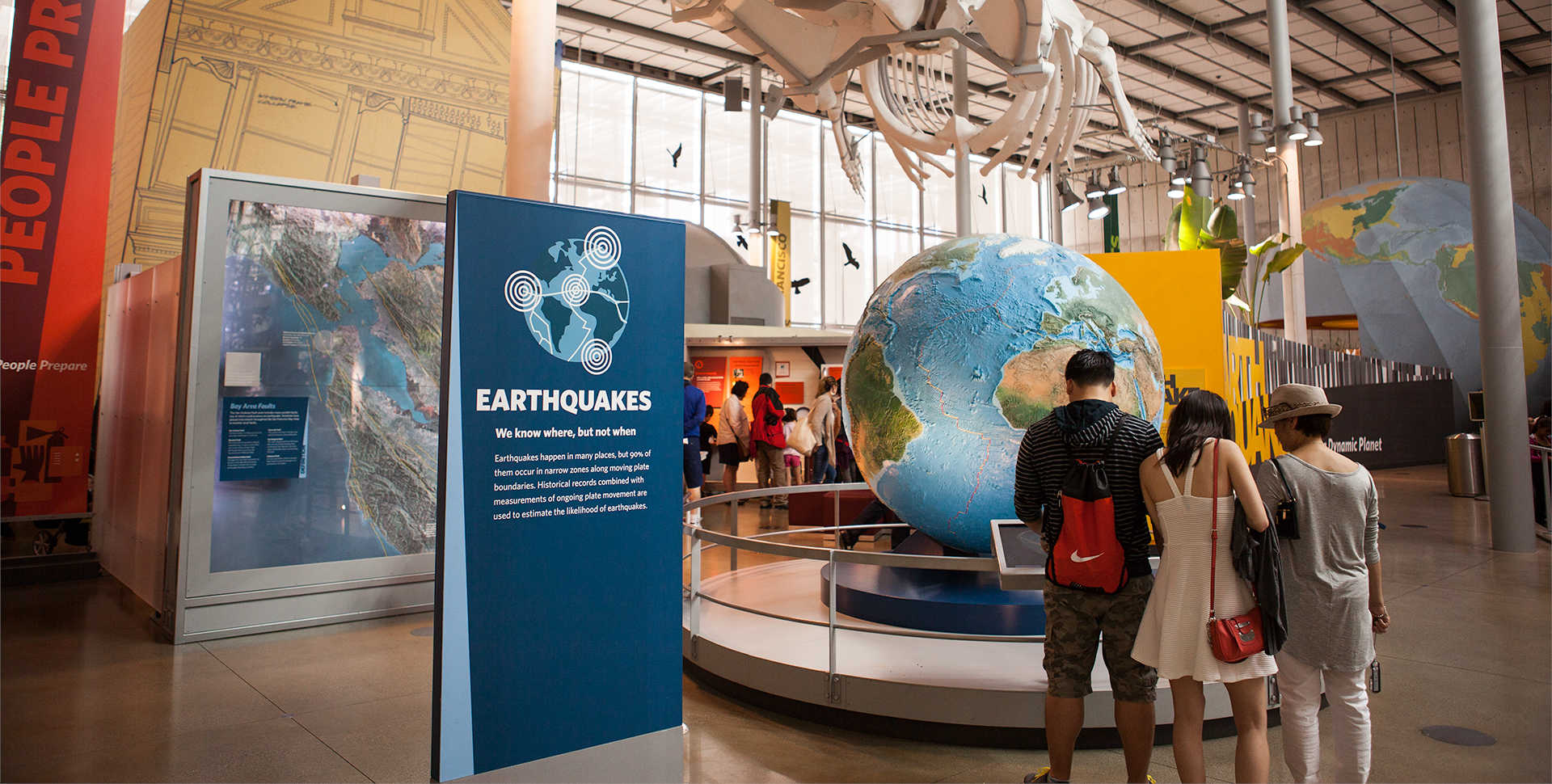 Visitors examine a giant globe at Earthquake, a major exhibit at the California Academy of Sciences