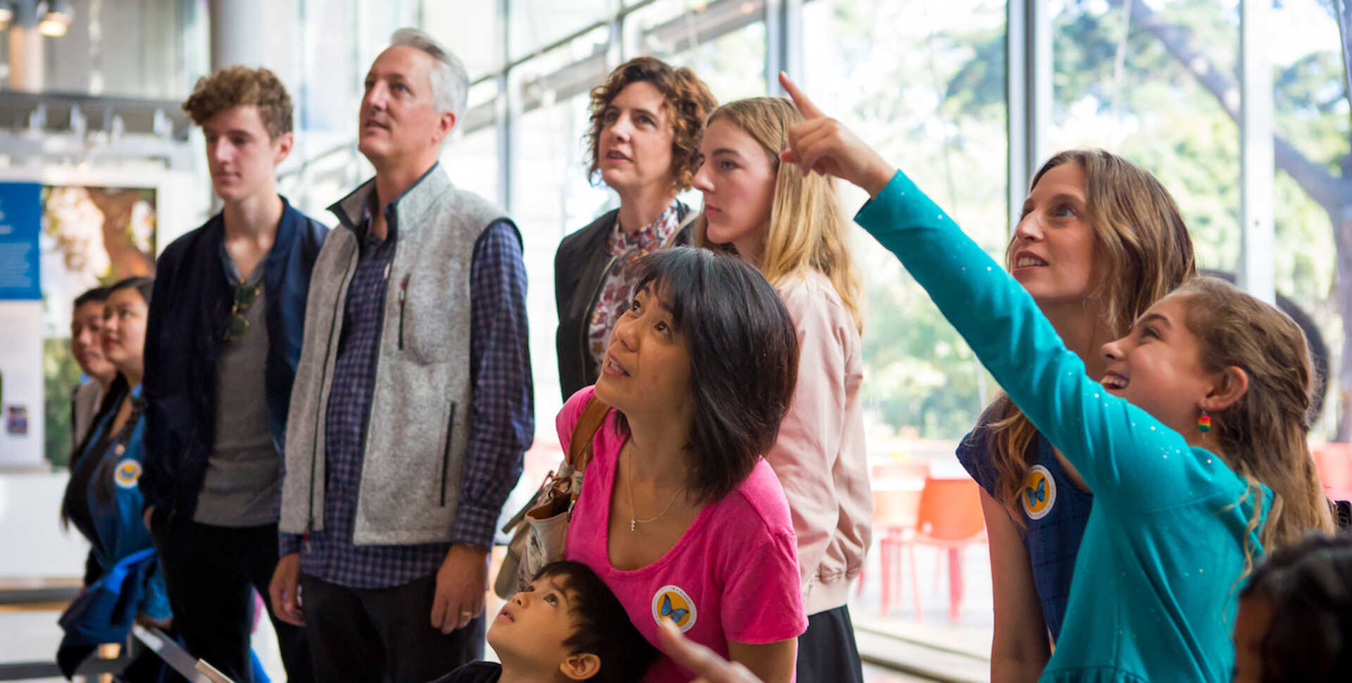Members watching Gouldian finches in the Color of Life exhibit at the California Academy of Sciences