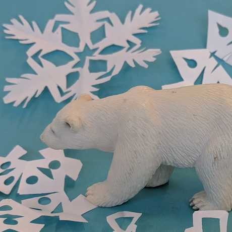 polar bear walking through paper snow flakes