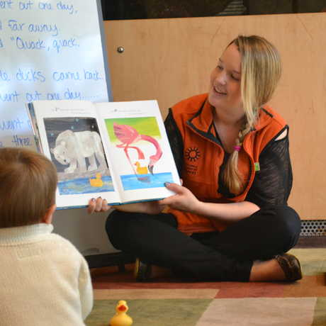 A photo of a California Academy of Sciences employee reading a story to young children.