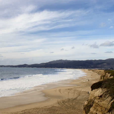 Sandy beach and tidal zone with rocky cliffs on a sunny day