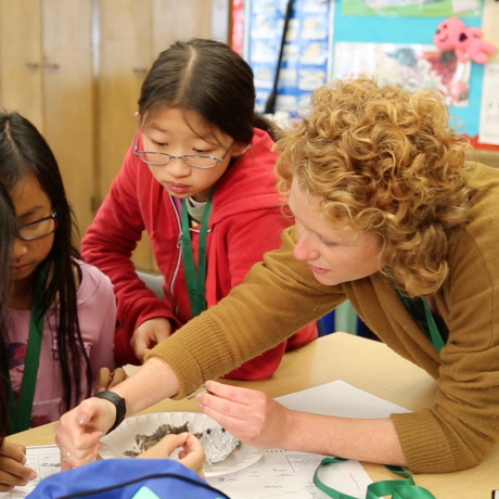 Teacher helping students with a science project