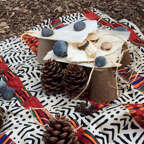 pine cones, rocks, and other natural items on a blanket outside