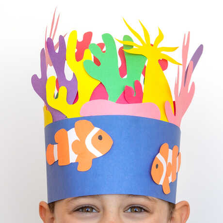 A boy wears a hand-made paper crown featuring a coral reef scene