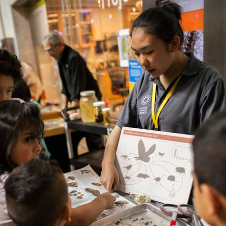 A docent outside the lab talks to children about birds.