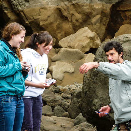 Students in the Summer Systematics Institute are shown a sea creature by a researcher.