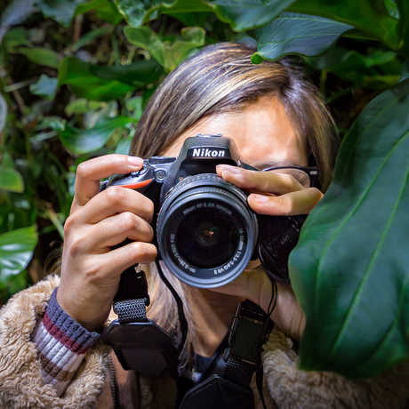 A photographer points her camera at the viewer