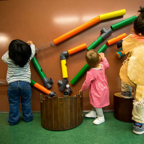 Kids playing with the colorful wall puzzle in the new Curiosity Grove