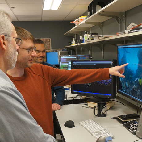 Three Academy designers examine their digital creations on a trio of computer monitors