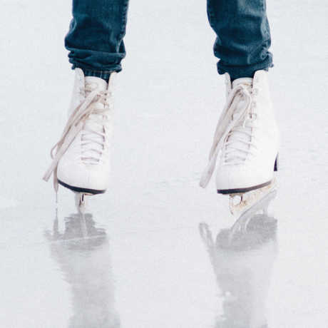 White ice skates reflecting on an ice rink