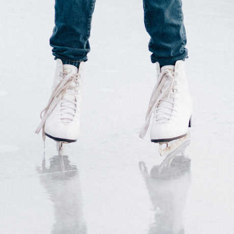 An ice skater and her shadow on an ice rink.