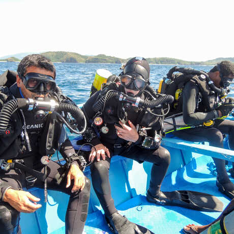 A trio of Academy scientists on a boat in scuba gear, ready to dive Palau.