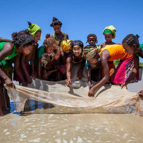 Young women in Madagascar use a fishing net