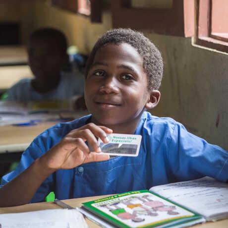 A boy in a school classroom in São Tomé studies local animals