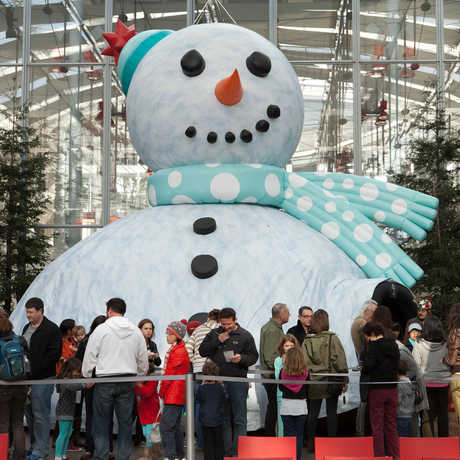 Guests line up to enter the giant Snowman Theater inside the Academy's Piazza