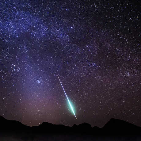 A brilliant white streak of a meteor heading down from a starry night sky