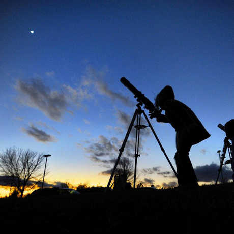 Telescope user looks up at a dark blue night sky