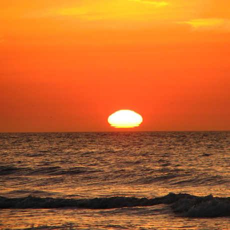 Sun setting on the horizon over the ocean and an orange sky
