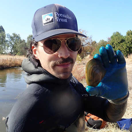 Wildlife ecologist Jonathan Young stands by a pond holding up a mussel