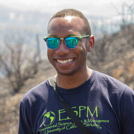 PhD candidate Kendall Calhoun stands on a mountain slope that experienced a wildfire