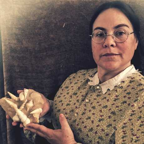 Actress portraying Paleontologist Mary Anning holding fossilized sea shells