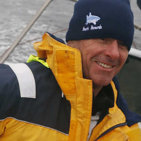 Dressed in a bright yellow windbreaker, David McGuire sits on a boat in stormy weather smiling