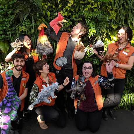 Museum staff holding dinosaur puppets