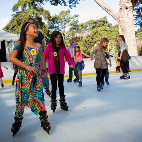 Girl in tie-dye dress ice skates gleefully at the Academy ice rink