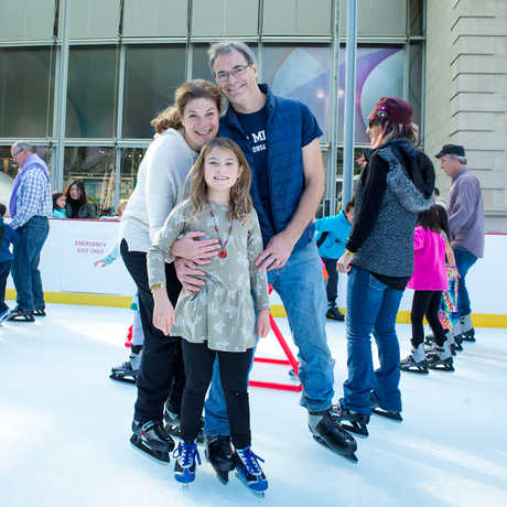 Member family posing for the camera at the Academy's outdoor ice rink