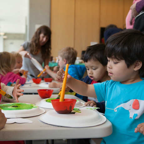 A boy paints at a family craft activity at the museum