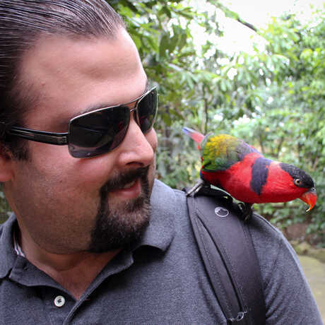 Jason Goldman with a colorful bird on his shoulder