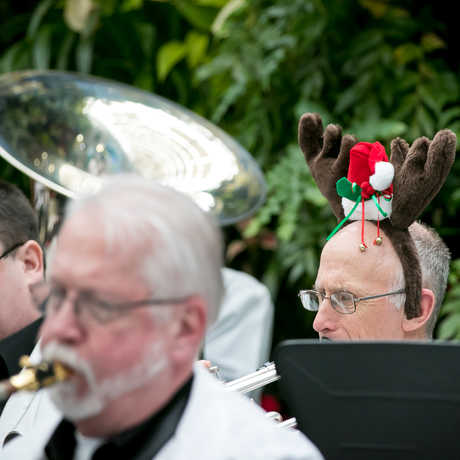 Musician wearing holiday reindeer ears plays trumpet in live band