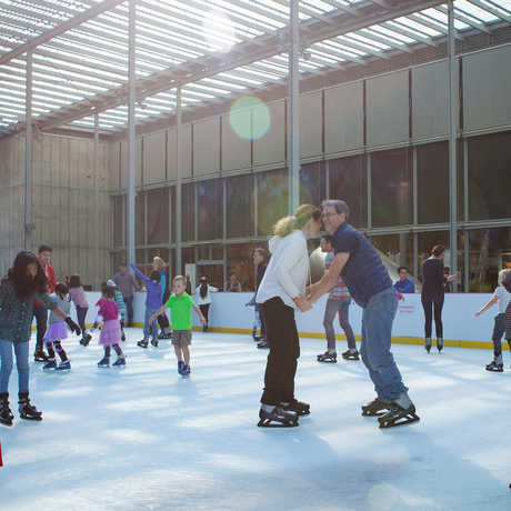 A couple holds hands on the Academy's Holiday Ice Rink