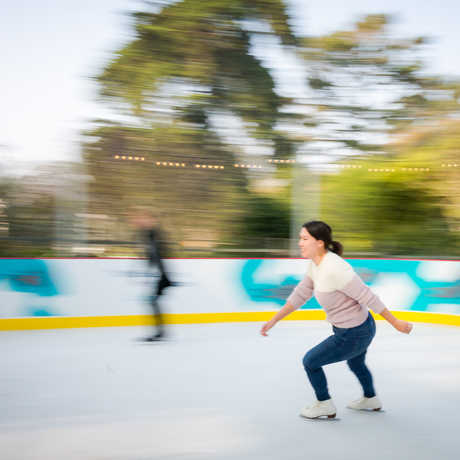 Woman ice skating with blurry background at Academy outdoor ice rink