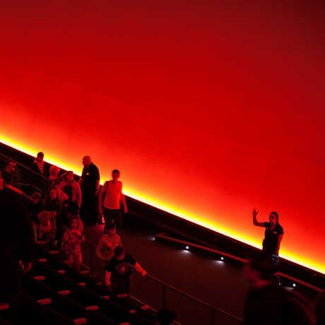 A crowd listens to a planetarium presented inside the vast, all-digital dome of Morrison Planetarium.