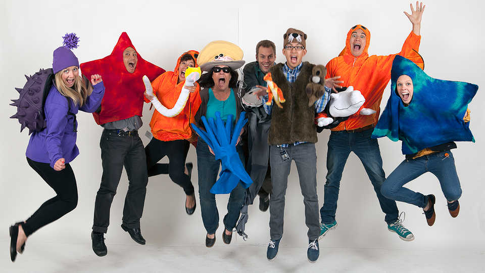 Staff in a variety of animal costumes joyously jump in midair