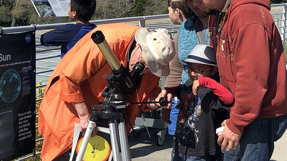An Academy Docent helps Astronomy Day visitors observe the Sun safely.