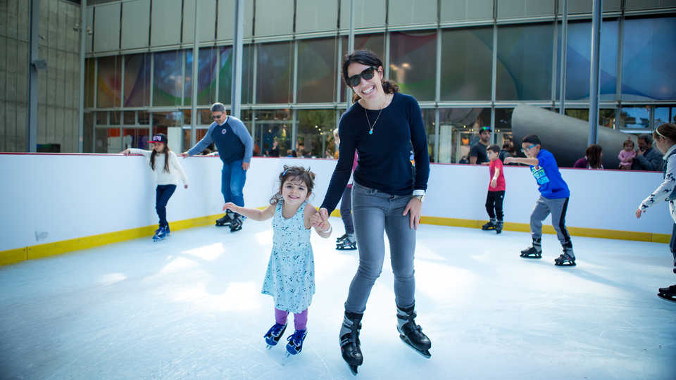 A mother and daughter ice skate at the Academy's holiday ice rink
