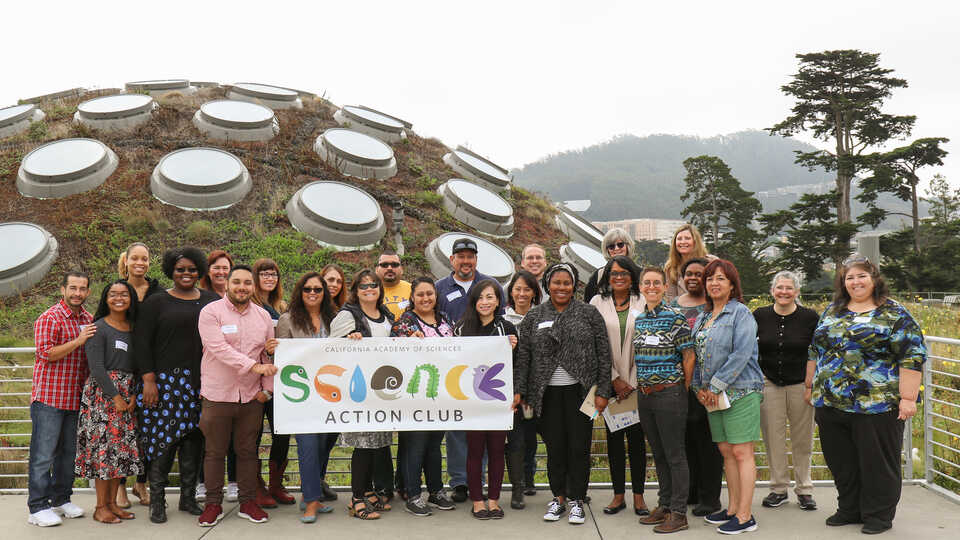 Group of Science Action Club educators holding SAC banner atop Academy Living Roof